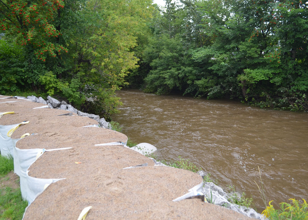 Barrière temporaire installée le long d'une rivière menaçante